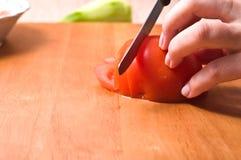 Hände, die Tomate schneiden Stockfotografie