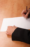 Hände, die unbelegtes Papier unterzeichnen Lizenzfreies Stockfoto