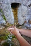 Hände, die unter Wasserquelle sich waschen Stockbilder