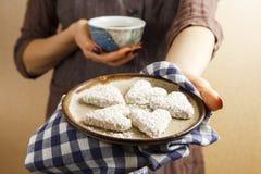 Hände, die Valentinsgrußkeks und -kaffee halten Lizenzfreies Stockfoto
