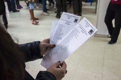 Hände, die verschiedene Stimmzettel von Kandidaten am spanischen Parlamentswahltag in Madrid, Spanien halten Stockbild