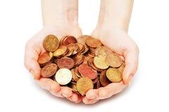 Hände, die viele Münzen isola anhalten Stockfotografie