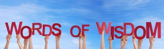 Hände, die Wörter von Klugheit im Himmel halten Stockfotografie