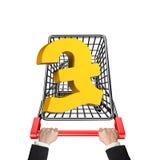 Hände, die Warenkorb mit goldenem Symbol des Pfunds 3D drücken Lizenzfreies Stockfoto