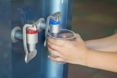 Hände, die Wasser von der Wasserkühlungsmaschine gießen Füllendes Glas vom Wasserspender, Nahaufnahme stockbilder