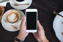 Hände, die weißen Handy mit leerem schwarzem Schirm mit Kaffeetassen auf Holztisch im Restaurant halten Stockfotografie