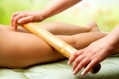 Hände, die weibliche Beine mit Bambus massieren. Lizenzfreie Stockbilder