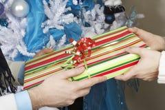 Hände, die Weihnachtsbaum austauschen Stockfotos