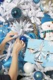 Hände, die Weihnachtsbaum verzieren Stockbilder