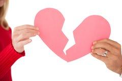 Hände, die zwei Hälften des defekten Herzens halten Stockfoto