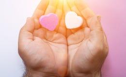 Hände, die zwei Herz-förmige Süßigkeiten halten stockfotos