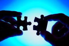 Hände, die zwei Puzzlespielstücken sich anschließen. Lizenzfreies Stockbild
