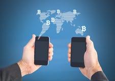 Hände, die zwei Telefone mit Stückchenmünzenweltkarte halten Lizenzfreie Stockbilder