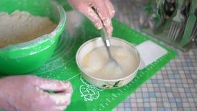 Hände einer älteren Frau an der Hilfe einer Löffel-Mischung in eine Platten-den Bestandteilen für einen Teig stock video footage
