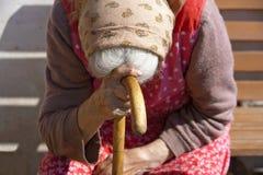 Hände einer alten Frau mit einem Stock Stockfoto
