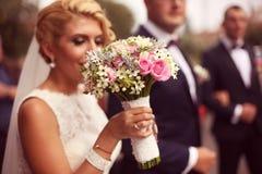 Hände einer Braut, die ihren Hochzeitsblumenstrauß hält Lizenzfreie Stockfotografie