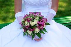 Hände einer Braut mit einem Blumenstrauß Lizenzfreies Stockbild