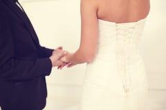 Hände einer Braut- und Bräutigamholding Stockfotos