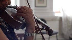 Hände einer Frau, die eine Geige mit Geigenbogen hält und auf Konzertnahaufnahme spielt stock footage