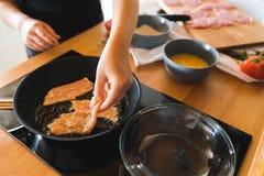 Hände einer Frau setzten Stücke Truthahnfleisch in eine Bratpfanne ein Lizenzfreies Stockbild