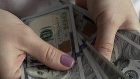 Hände einer jungen Frau, die aus Dollarscheinen zählt stock video