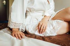 Hände einer jungen Frau legen auf ihre Beine, sie sitzt auf dem Stuhl stockfoto