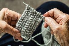 Hände eines älteren Frauenstrickens Stockfotos