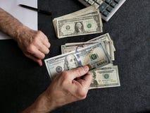 Hände eines älteren Mannes, der amerikanische Dollarbanknoten zählt stockbild
