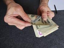 Hände eines älteren Mannes, der amerikanische Dollarbanknoten zählt lizenzfreies stockbild