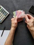 Hände eines älteren Mannes, der chilenische Banknoten zählt lizenzfreie stockbilder