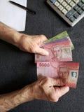 Hände eines älteren Mannes, der chilenische Banknoten zählt stockfotos