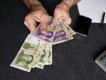 Hände eines älteren Mannes, der chinesische Banknoten zählt lizenzfreie stockbilder