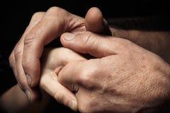Hände eines älteren Mannes, der die Hand eines jüngeren Mannes hält Lizenzfreie Stockbilder