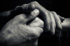 Hände eines älteren Mannes, der die Hand eines jüngeren Mannes hält Lizenzfreies Stockbild