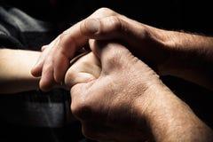 Hände eines älteren Mannes, der die Hand eines jüngeren Mannes hält Stockbilder