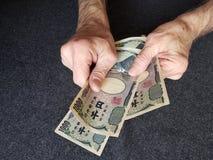 Hände eines älteren Mannes, der japanische Banknoten hält stockfoto