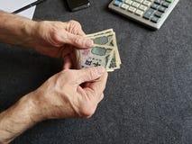 Hände eines älteren Mannes, der japanische Banknoten zählt stockfotografie