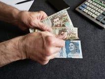 Hände eines älteren Mannes, der kolumbianische Banknoten hält stockbilder