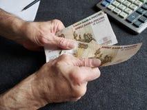 Hände eines älteren Mannes, der russische Banknoten zählt lizenzfreie stockbilder