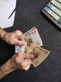Hände eines älteren Mannes, der russische Banknoten zählt stockfotos
