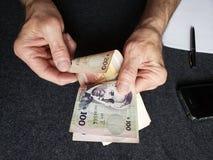 Hände eines älteren Mannes, der uruguayische Banknoten zählt lizenzfreies stockbild