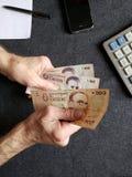 Hände eines älteren Mannes, der uruguayische Banknoten zählt lizenzfreie stockfotografie