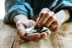 Hände eines alten Mannes auf der hölzernen Tabelle stockbild
