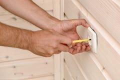 Hände eines Elektrikers, der einen Sockel, eine Nahaufnahme herausschneiden installiert lizenzfreie stockbilder