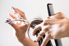 Hände eines Friseurszutathaares mit einem Kamm und Scheren Stockfotografie