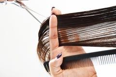 Hände eines Friseurszutathaares mit einem Kamm und Scheren Stockbild
