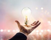 Hände eines Geschäftsmannes, der in Richtung zu zur Glühlampe auf hölzernem erreicht Lizenzfreie Stockbilder