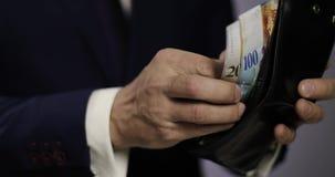 Hände eines Geschäftsmannes gehen Schweizer Franken von ihrer Geldbörse hinaus stock footage