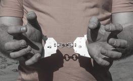 Hände eines groben Mannes in den Handschellen hinter seiner Rückseite auf einem orange T-Shirt Kriminelle Bestrafung der Gefangen lizenzfreies stockfoto