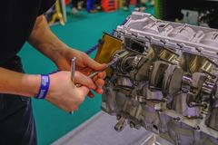 Hände eines Ingenieurs, der einen Automotor aufbaut stockbilder
